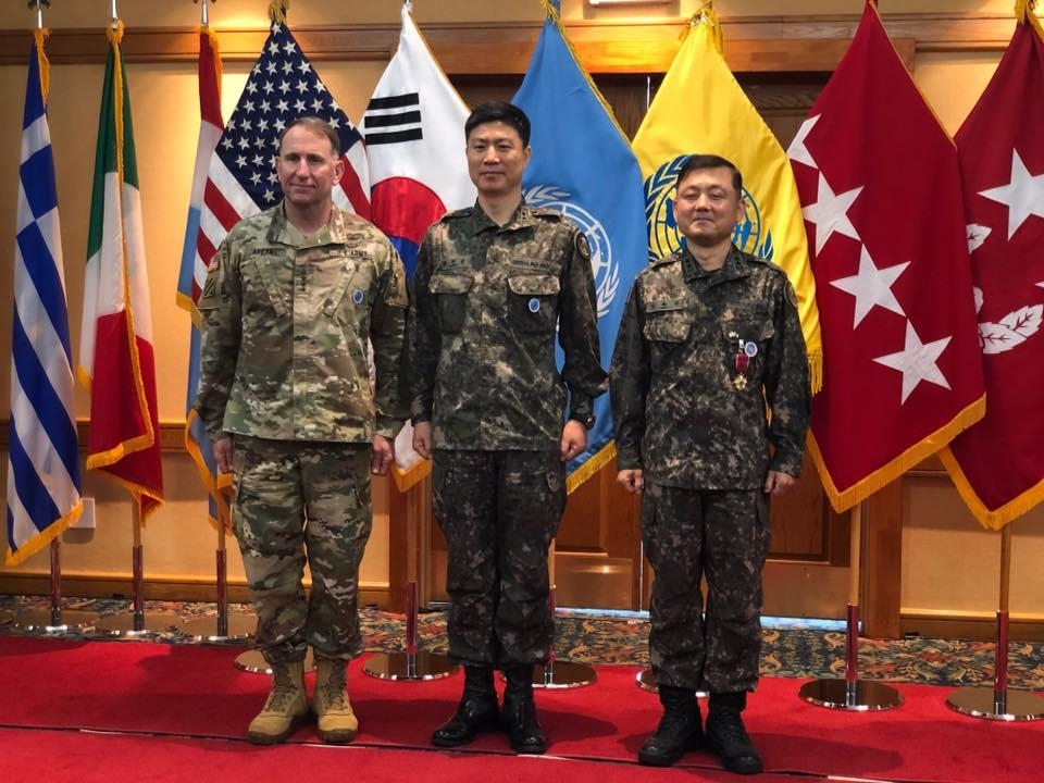 In this photo, captured from the Facebook page of the United Nations Command (UNC), Army Maj. Gen. Kang In-soon (C) poses for a photo during an inauguration ceremony to take office as the new senior member of the command's Military Armistice Commission on May 27, 2020. To his left is UNC Commander Gen. Robert Abrams. (PHOTO NOT FOR SALE) (Yonhap)