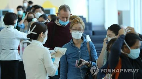 Passengers wearing masks undergo boarding checks at Incheon International Airport, west of Seoul, on May 27, 2020, when a rule requiring all passengers to wear masks on domestic and international flights was implemented. (Yonhap)