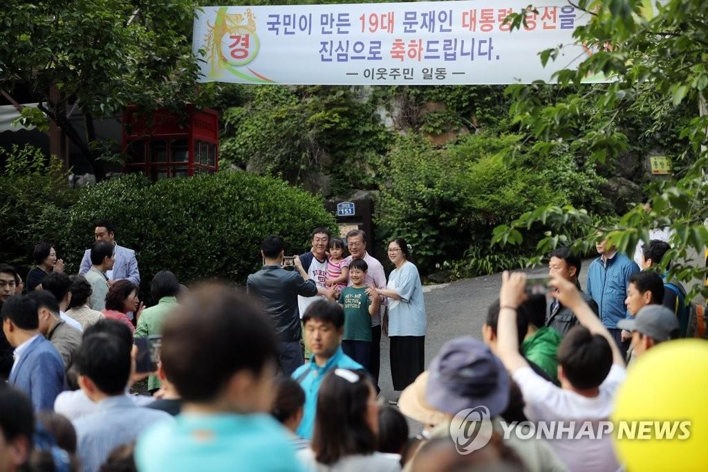 This undated file photo shows President Moon Jae-in taking a commemorative photo with citizens in front of his private home in Yangsang, South Gyeongsang Province. (Yonhap)