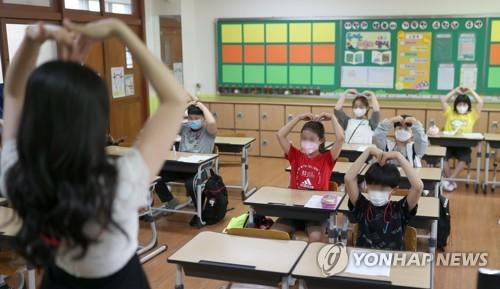 Students exchange greetings with their teacher while seated in a zigzag arrangement at Samsung Elementary School in Gimhae, 449 kilometers southeast of Seoul, on June 3, 2020. (Yonhap)