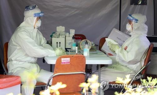 Screening station workers use ice packs to ward off the heat in Daegu on June 10, 2020, as the temperature soared above 35 C in the southeastern city. (Yonhap)