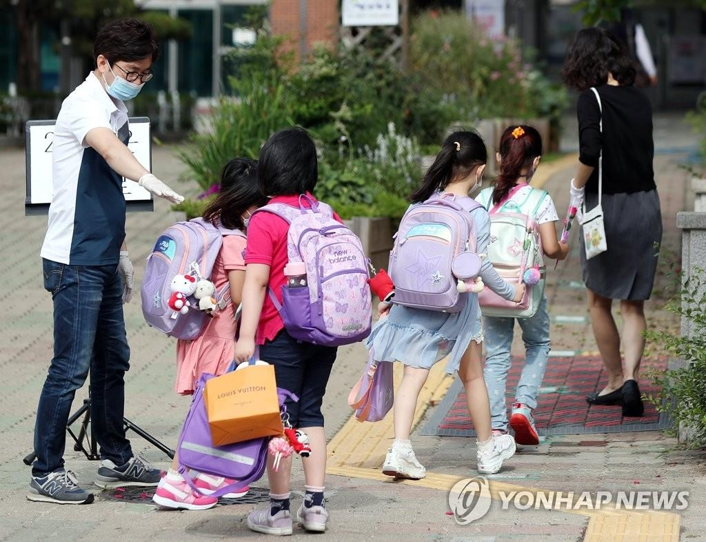 Pupils enter school in Bucheon, Gyeonggi Province, on June 11, 2020. (Yonhap)