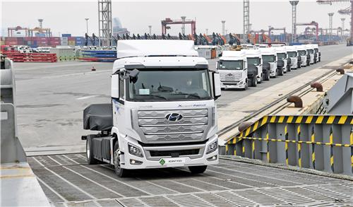 This photo taken on July 6, 2020, and provided by Hyundai Motor shows XCIENT Fuel Cell hydrogen trucks being loaded onto the Global Superior roll-on roll-off ship heading to Switzerland at a port in Gwangyang, 423 kilometers south of Seoul. (PHOTO NOT FOR SALE) (Yonhap)