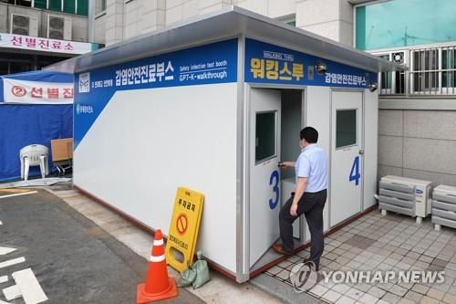 This photo provided by Dongdaemun Ward Office shows a person walking into a walk-thru clinic in Seoul on July 7, 2020, to be tested for the coronavirus. (Yonhap)