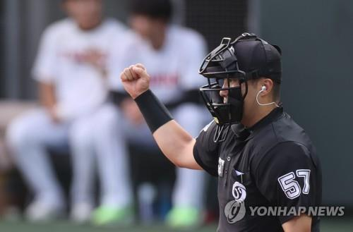 The home plate umpire calls a strike, aided by so-called robot umpires, during the Futures League game between the Hanwha Eagles and LG Twins at LG Champions Park in Icheon, southeast of Seoul, on Aug. 4, 2020.