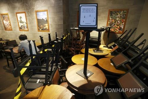Chairs and tables are stacked up as part of social distancing measures at a Starbucks store in Seoul on Aug. 18, 2020. (Yonhap)