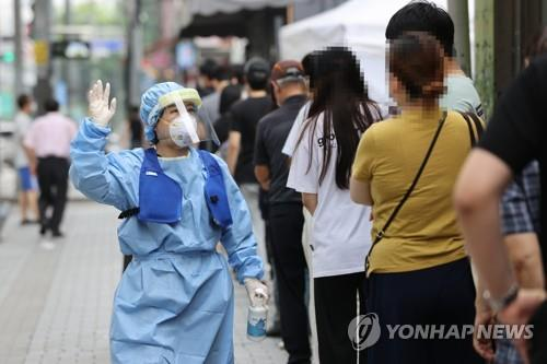 Citizens wait in line to receive coronavirus tests at a screening center in Seoul's northern ward of Seongbuk on Aug. 20, 2020. (Yonhap)