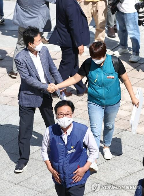 Kwon Jeong-oh (L), head of the Korean Teachers and Education Workers Union (KTU) shakes hands with a union member outside the Supreme Court on Sept. 3, 2020. (Yonhap)