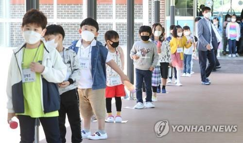Students wait in line while keeping distance from each other to eat their first school lunch at the cafeteria of Geumbyeong Elementary School in Chuncheon, 85 kilometers northeast of Seoul, on May 27, 2020. (Yonhap)