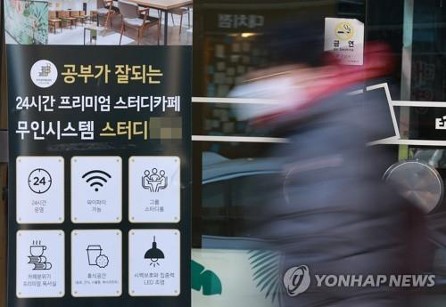 A student walks by a cafe in southern Seoul on Dec. 4, 2020. (Yonhap)