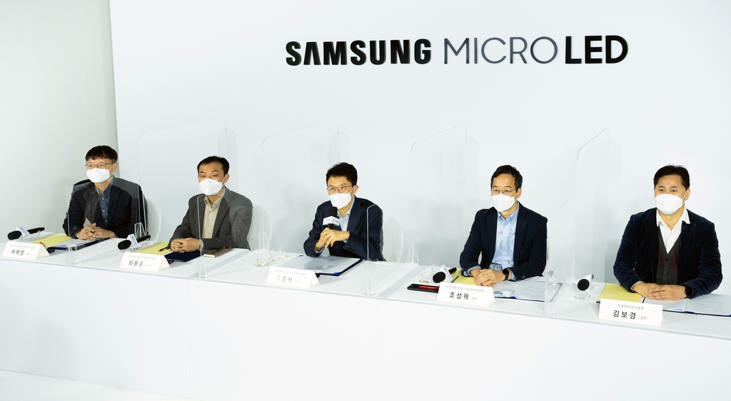 This photo provided by Samsung Electronics Co. on Dec. 10, 2020, shows company executives explaining Samsung's new 110-inch Micro LED TV at an online event in South Korea. (PHOTO NOT FOR SALE) (Yonhap)