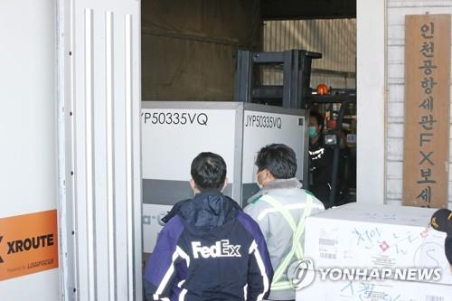 Workers transport the first shipment of Moderna's coronavirus vaccine for the U.S. Forces Korea (USFK) onto a truck after it was unloaded from a FedEx cargo plane at Incheon International Airport, west of Seoul, amid the COVID-19 pandemic on Dec. 25, 2020. (Yonhap)