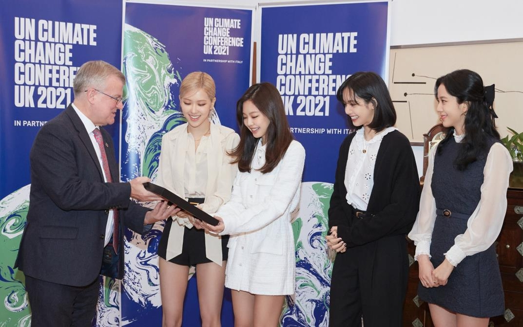 This photo, provided by YG Entertainment, shows BLACKPINK receiving a letter from Simon Smith, British ambassador to South Korea, during an event at the British Embassy in Seoul. (PHOTO NOT FOR SALE) (Yonhap)