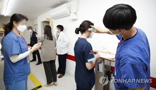 A medical worker (R) checks the body temperature of people who are set to receive additional vaccine jabs at a vaccination center in Seoul on Oct. 12, 2021. Health authorities started giving additional COVID-19 shots to people who were fully vaccinated six months ago the same day. (Pool photo) (Yonhap)