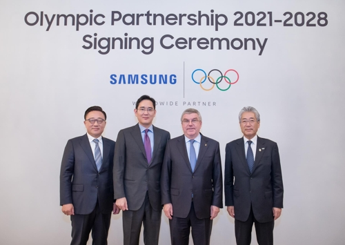 De gauche à droite: le président de la branche des communications mobiles de Samsung Electronics Koh Dong-jin, le président de Samsung Electronics Lee Jae-yong, le directeur du CIO Thomas Bach et le président de la commission du marketing du CIO Tsunekazu Takeda.