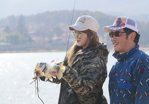 프로 낚시인 김욱 이사와 박지숙 씨가 배스를 잡고 기뻐하고 있다 [사진/성연재 기자]