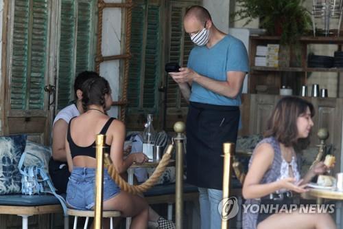 미국 캘리포니아 로스앤젤레스의 한 식당에서 웨이터가 마스크를 쓴 채 손님 주문을 받고 있다. [로이터=연합뉴스 자료사진]