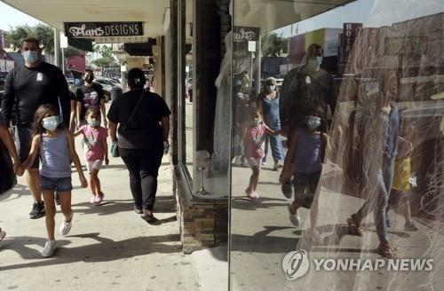 16일(현지시간) 미 텍사스주 매켈런의 한 상점 앞을 마스크를 쓴 시민들이 지나가고 있다. [AP=연합뉴스]