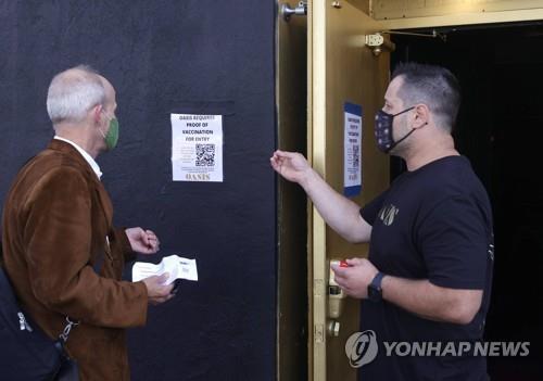 지난달 29일 미 샌프란시스코의 한 업소에서 종업원이 고객에게 입장하려면 백신 접종카드가 필요하다고 안내하고 있다. [AFP=연합뉴스]