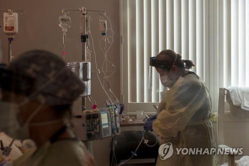 지난달 미 캘리포니아 소노라의 어드밴티스트 헬스 병원 중환자실에서 한 간호사가 코로나19 환자의 상태를 살펴보고 있다. [AFP=연합뉴스]