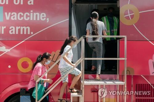 미국에서 12세 이상 화이자 백신 접종 승인 이후 지난 7월 백신 접종 차량에 올라타는 가족 [AFP=연합뉴스]