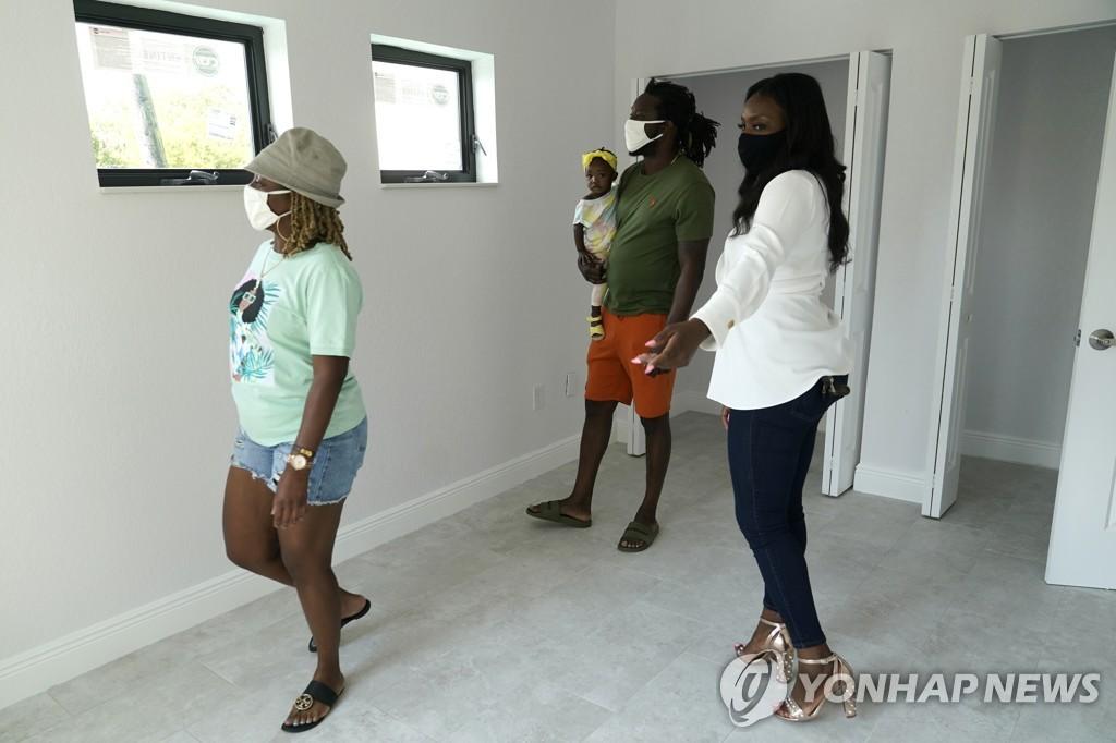 미국 마이애미의 집을 보러 온 가족과 부동산 중개인(우측)