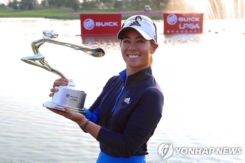 In this AFP photo, Danielle Kang of the United States holds the champion's trophy after winning the Buick LPGA Shanghai golf tournament at Qizhong Garden Golf Club in Shanghai on Oct. 20, 2019. (Yonhap)