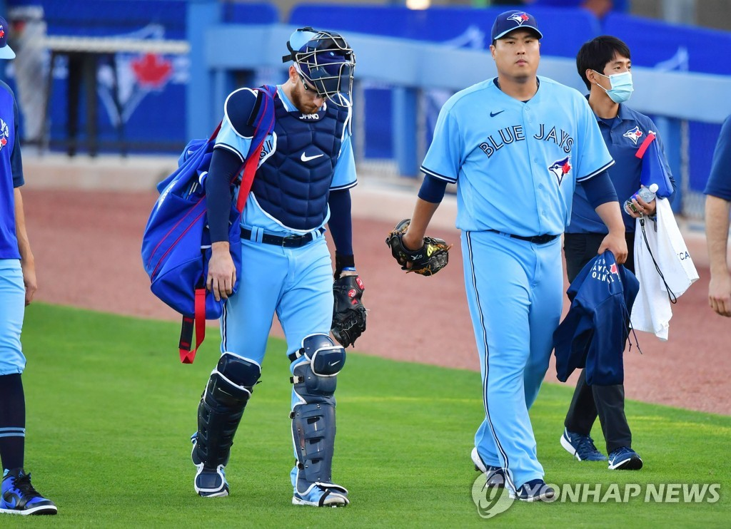 In this Getty Images photo, Ryu Hyun-jin of the Toronto Blue Jays (2nd from R) walks to the dugout alongside his catcher Danny Jansen (L) before a Major League Baseball regular season game against the New York Yankees at TD Ballpark in Dunedin, Florida, on April 13, 2021. (Yonhap)