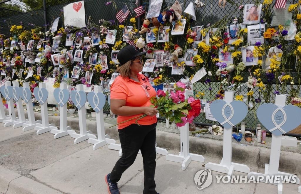 미국 플로리다주(州) 마이애미데이드 카운티 서프사이드 아파트 붕괴사고 희생자를 기리는 인근 성당에 마련된 추모 벽에 7일 한 여성이 헌화하고 있다. [UPI=연합뉴스]