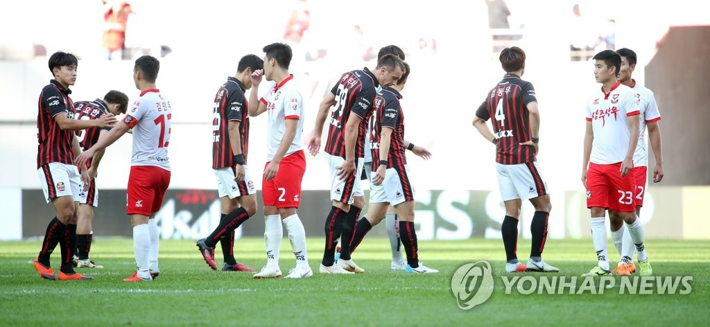 In this file photo taken on Sept. 30, 2018, players from FC Seoul (in red and black) and Sangju Sangmu react after playing to a 2-2 draw in their K League 1 match at Seoul World Cup Stadium in Seoul. (Yonhap)