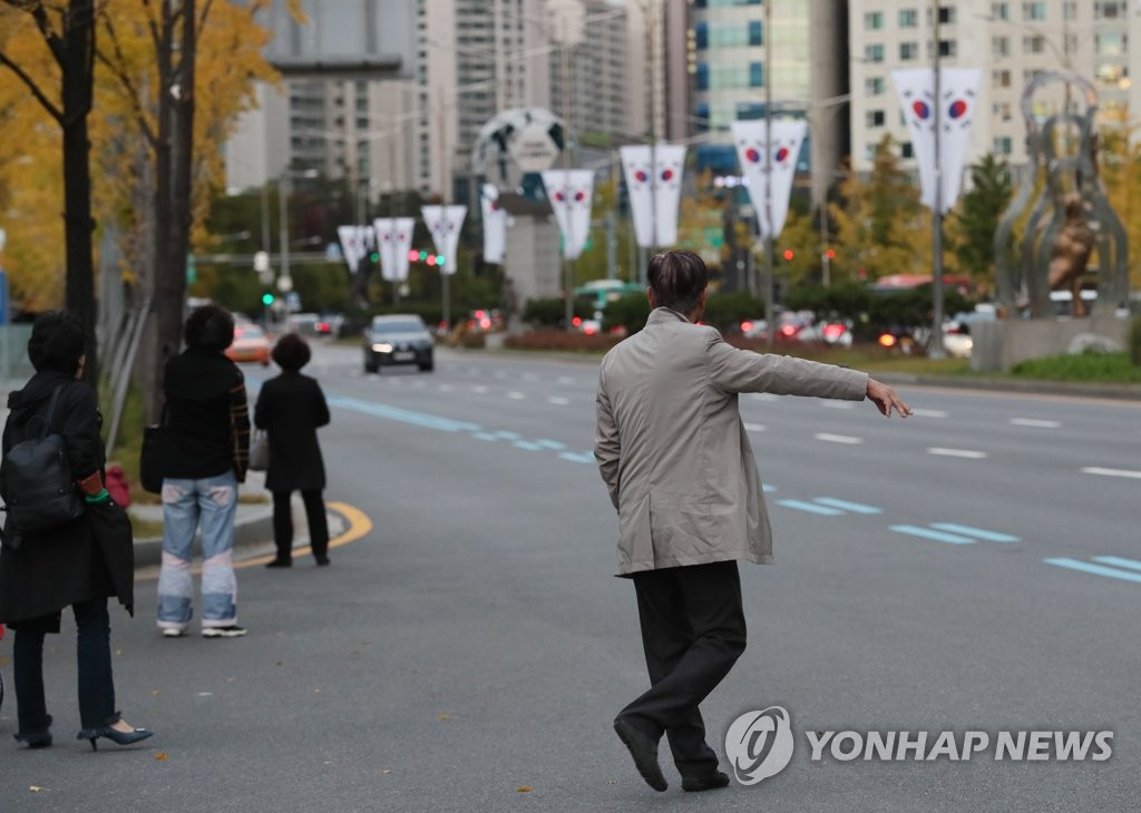 This photo taken Oct. 18, 2018, shows several people trying to grab a taxi in eastern Seoul. (Yonhap)
