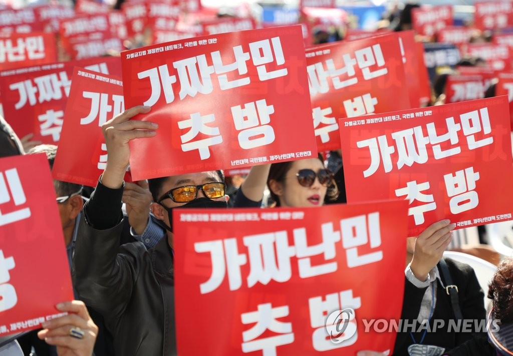 "A group of South Korean activists stages a rally against asylum seekers, holding signs reading ""Deport fake refugees,"" in Seoul on Oct. 20, 2018. (Yonhap)"