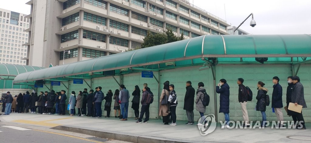 This file photo taken Nov. 29, 2018, shows people forming a long queue to apply for a U.S. visa in front of the U.S. Embassy in Seoul, ahead of the start of winter vacation season.