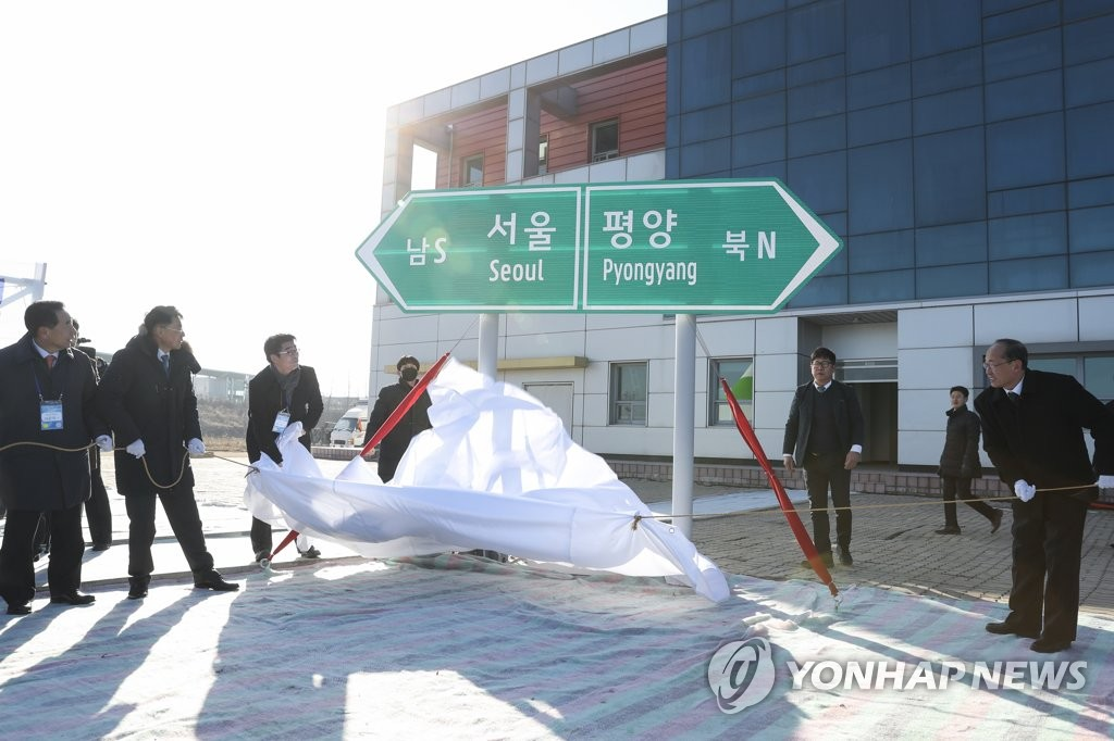 Participants unveil a road sign during a groundbreaking ceremony for a project to modernize and connect roads and railways over the border between the Koreas at Panmun Station in the North's border town of Kaesong on Dec. 26, 2018, in this photo provided by the ministry. (PHOTO NOT FOR SALE) (Yonhap)