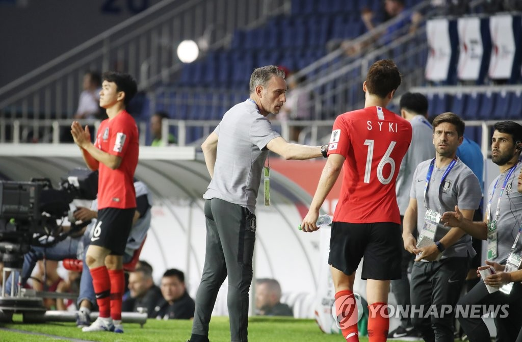 In this file photo taken on Jan. 7, 2019, South Korea national football team head coach Paulo Bento (C) speaks to Ki Sung-yueng (R) during a Group C match against the Philippines at the AFC Asian Cup at Al Maktoum Stadium in Dubai, the United Arab Emirates. (Yonhap)