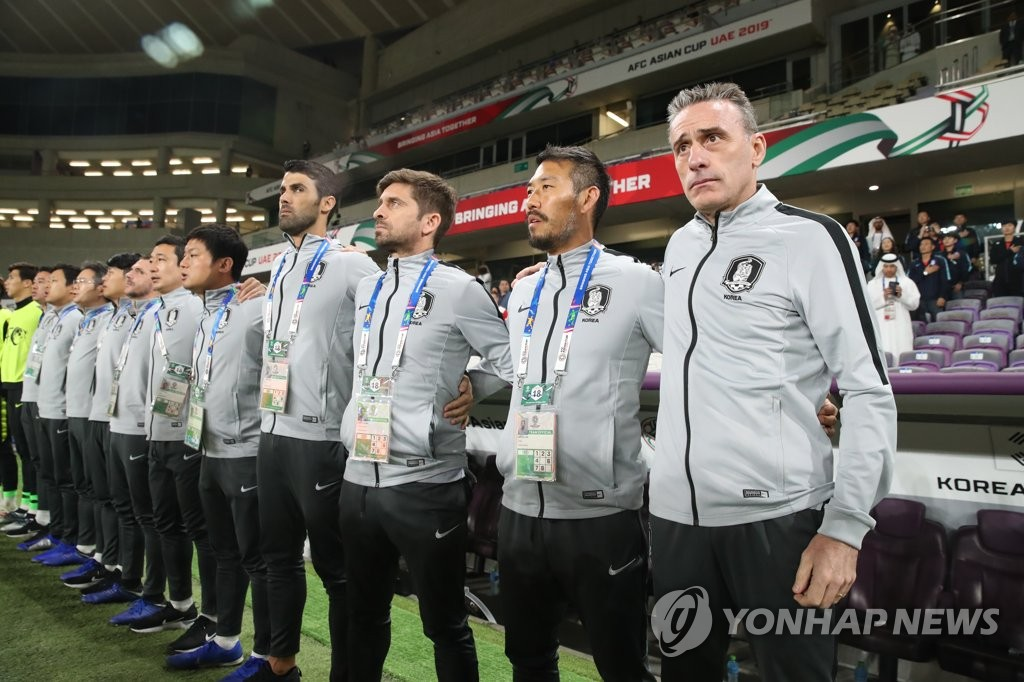 Paulo Bento (R), head coach of the South Korean men's football team, stands for the national anthem with his staff before the start of Group C match against Kyrgyzstan at the Asian Football Confederation Asian Cup at Hazza Bin Zayed Stadium in Al Ain, the United Arab Emirates, on Jan. 11, 2019. (Yonhap)
