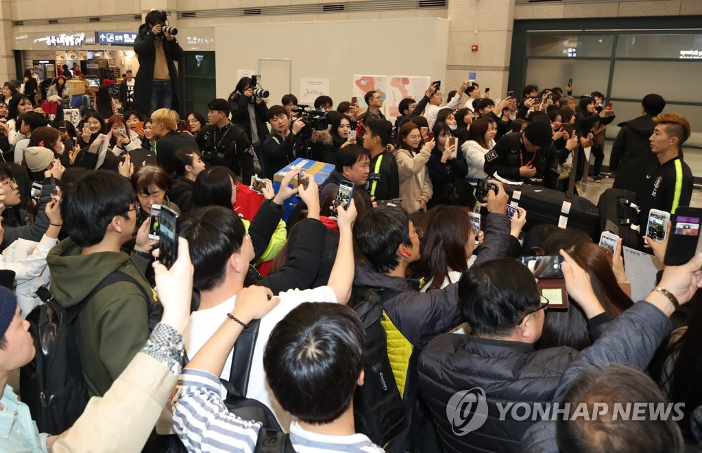 South Korean football fans take photo of the national football team players at Incheon International Airport in Incheon on Jan. 28, 2019. (Yonhap)