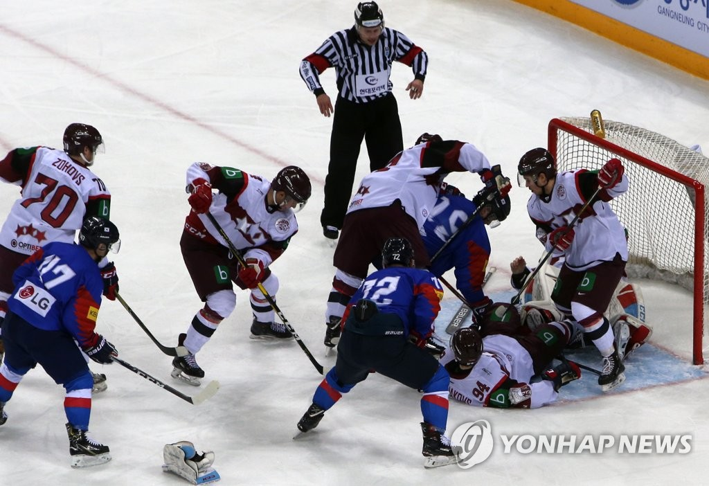Players for South Korea (in blue) and Latvia battle for the loose puck in front of the Latvian net during the opening match of the Legacy Cup men's hockey tournament at Gangneung Hockey Centre in Gangneung, 230 kilometers east of Seoul, on Feb. 6, 2019. (Yonhap)