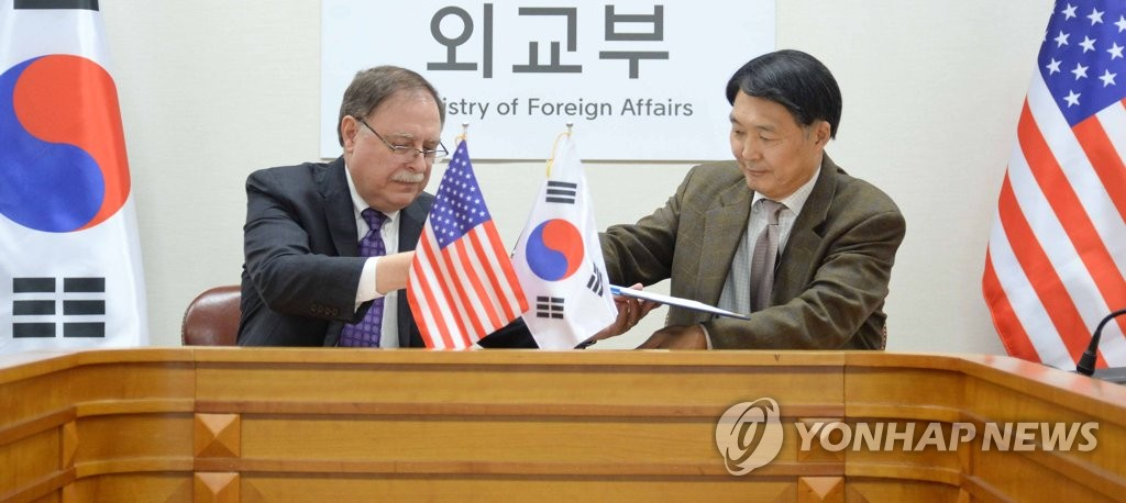 Chang Won-sam (R), South Korea's delegate to defense cost talks with the United States, exchanges a letter of accord with his counterpart Timothy Betts in a signing ceremony in Seoul on Feb. 10, 2019, in this photo provided by the foreign ministry. (Yonhap)
