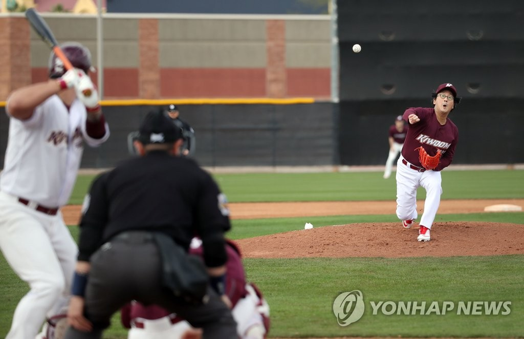 Hur Min (R), chairman of the board of directors for the Kiwoom Heroes baseball club, throws a pitch in a spring training intrasquad game at Peoria Sports Complex in Peoria, Arizona, on Feb. 17, 2019. (Yonhap)