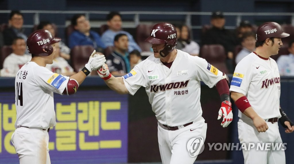 In this file photo from April 24, 2019, Jerry Sands of the Kiwoom Heroes (C) celebrates his grand slam against the Doosan Bears with teammate Seo Geon-chang (L) in the bottom of the seventh inning of a Korea Baseball Organization regular season game at Gocheok Sky Dome in Seoul. (Yonhap)