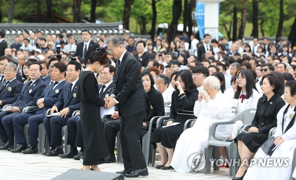 President Moon Jae-in holds the hands of a participant in the 1980 pro-democracy uprising during an anniversary ceremony held at the May 18th National Cemetery in Gwangju on May 18, 2019. (Yonhap)