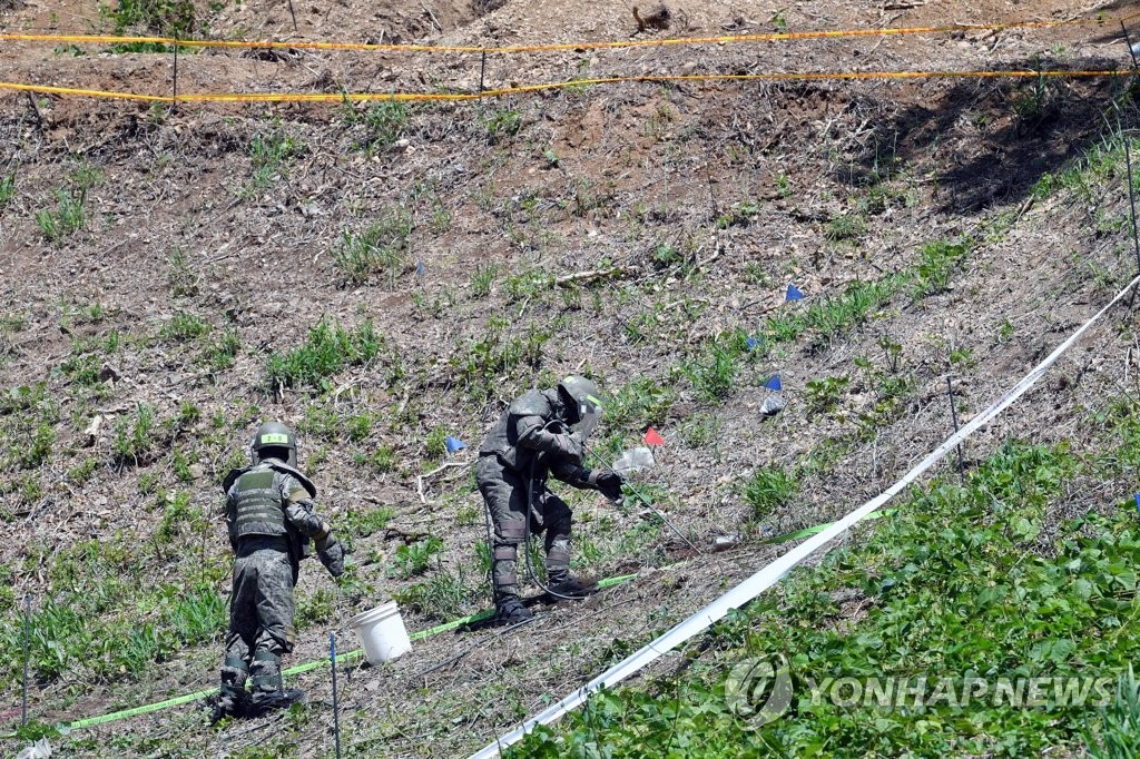 In this file photo, taken May 28, 2019, soldiers work to remove mines on Hwasalmeori (arrowhead) Hill inside the Demilitarized Zone bisecting the two Koreas. (Pool photo) (Yonhap)