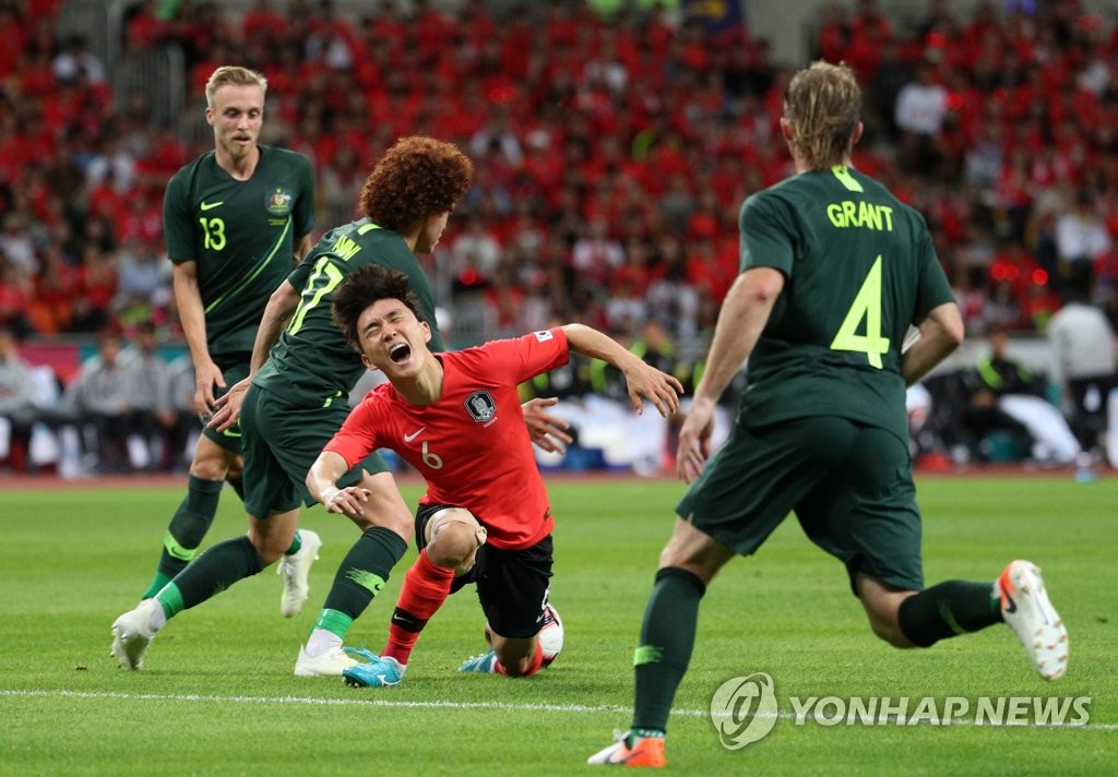 Hwang In-beom of South Korea (2nd from R) is tackled by Mustafa Amini of Australia in their men's football friendly match at Busan Asiad Main Stadium in Busan, 450 kilometers southeast of Seoul, on June 7, 2019. (Yonhap)