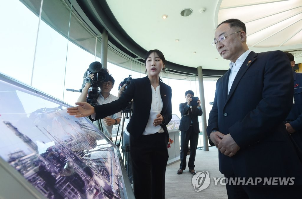 Hong Nam-ki (R), the minister of economy and finance, receives a briefing from an official at a SK Innovation plant in the southeastern industrial city of Ulsan on June 13, 2019, in this photo provided by the ministry. (PHOTO NOT FOR SALE) (Yonhap)