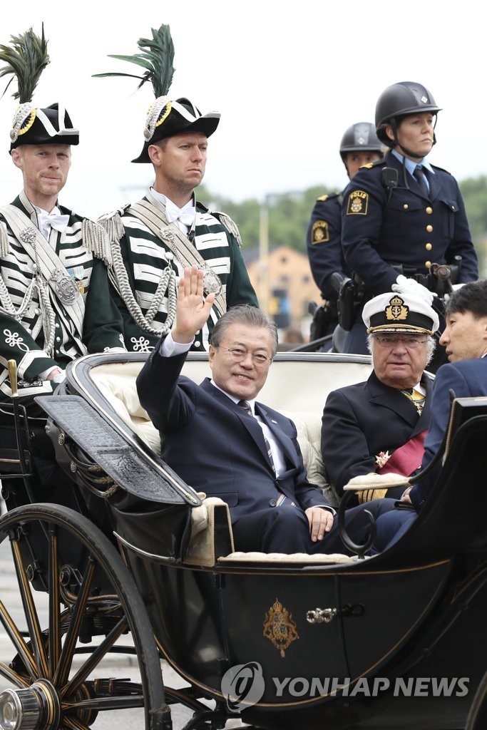 South Korean President Moon Jae-in (L) waves while riding through Stockholm streets in a carriage seated together with King Carl XVI Gustaf for a welcoming ceremony at the Royal Palace on June 14, 2019. (Yonhap)