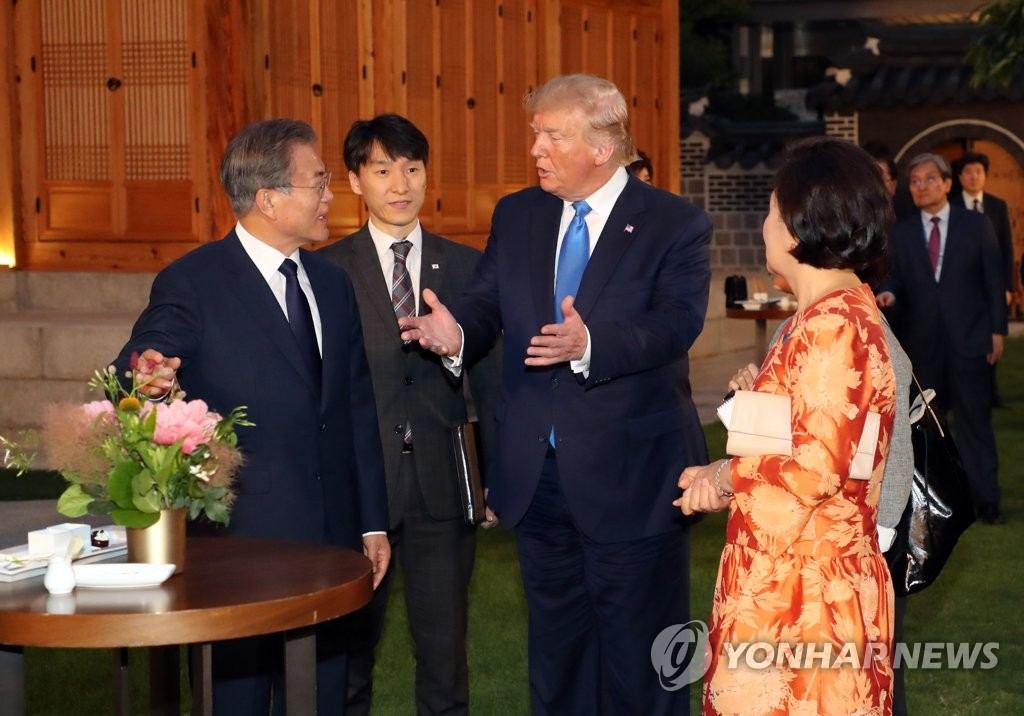 South Korean President Moon Jae-in (L) and U.S. President Donald Trump (3rd from L) converse during a friendly walk at the South Korean presidential office Cheong Wa Dae in Seoul on June 29, 2019, shortly after the U.S. leader arrived in South Korea's capital on a two-day visit for a summit with Moon and a trip to the Demilitarized Zone that divides the two Koreas. (Yonhap)