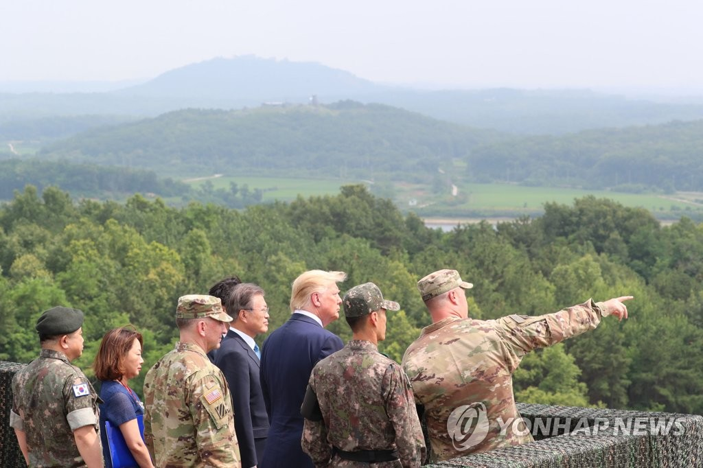 U.S. President Donald Trump (3rd from R) and South Korean President Moon Jae-in (C) peer into North Korea from Observation Post Ouellette at the DMZ on June 30, 2019. (Yonhap)