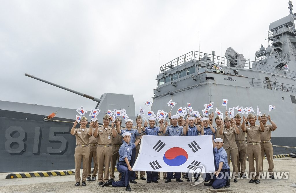 Sailors pose with flags to mark Liberation Day