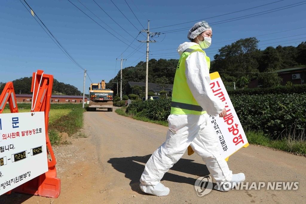 A quarantine official sets up a sign in Yeoncheon, north of Seoul, on Sept. 18, 2019, after the government implemented a nationwide standstill on all pig farms, slaughterhouses and feed factories following outbreaks of African swine fever in the country. (Yonhap)